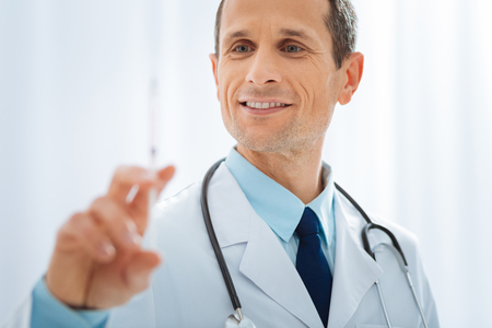 Wait a second. Positive delighted doctor keeping smile on his face and wrinkling forehead while treating his patient