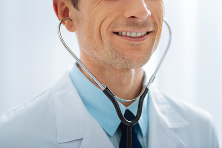 Be positive. Attractive man feeling happiness while using stethoscope and wearing medical uniform