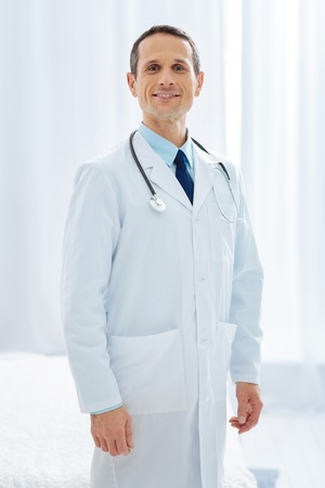 Be proud. Professional doctor keeping smile on his face and holding stethoscope on his neck while being in clinic Stock Photo