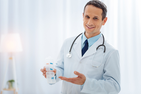 So easy. Attractive brunette male keeping smile on his face and having stethoscope around neck while posing on camera Stock Photo