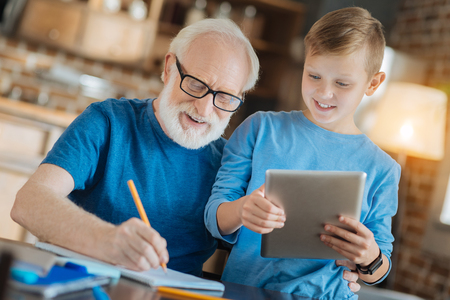 Joyful mood. Happy delighted elderly man smiling and taking notes while helping his grandson with studying