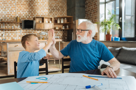 Great job. Happy positive senior man looking at his grandson and smiling while giving him high five