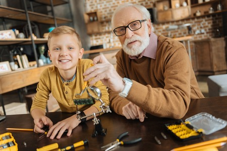 Family relations. Positive nice happy grandfather and grandson sitting at the table and looking at you while spending time together Standard-Bild