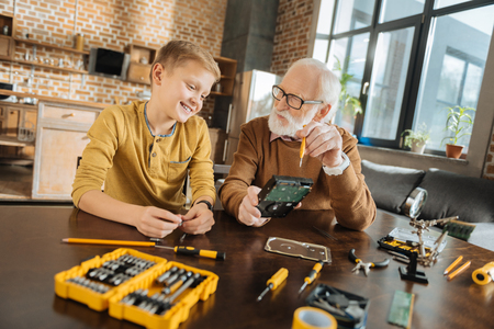 Pleasant communication. Delighted joyful positive girl sitting together with his grandfather and talking with his while learning how to fix things