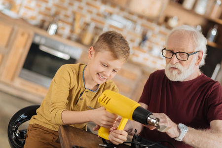 Professional instrument. Nice curious young boy holing a drill and looking at it while developing new skills