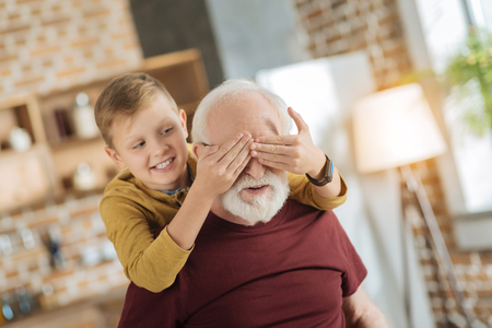 Dont open your eyes. Nice pleasant excited boy closing eyes of his grandfather and not letting hi, look while preparing a surprise Stock Photo
