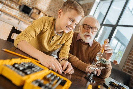 New knowledge. Happy delighted nice boy sitting together with his grandfather and smiling while learning new skills