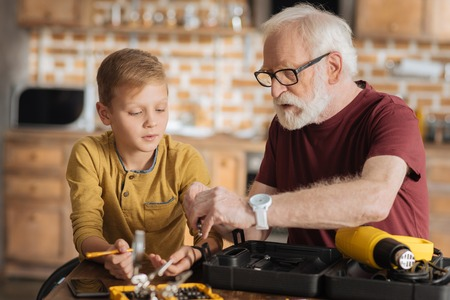 Skillful masters. Serious nice positive grandfather and grandson sitting at the table and looking at the drill while working together