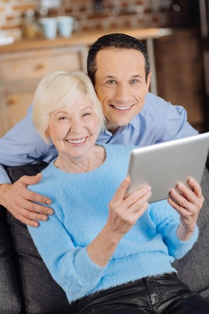 Happy together. Beautiful elderly woman and her young son smiling at the camera while watching a video on tablet together