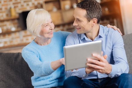 Being curious. Pleasant elderly woman sitting on the couch next to her son and asking him questions about how to use tablet while smiling