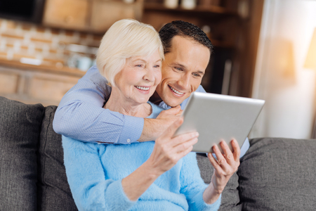 Amusing content. Charming young man hugging his mother from behind and watching a video on tablet together with her while both of them smiling brightly