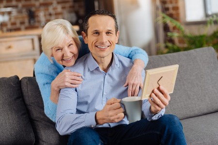 Remembering the past. Joyful elderly woman hugging her son from behind and posing for the camera together with him while he drinking coffee and looking at framed photo Фото со стока