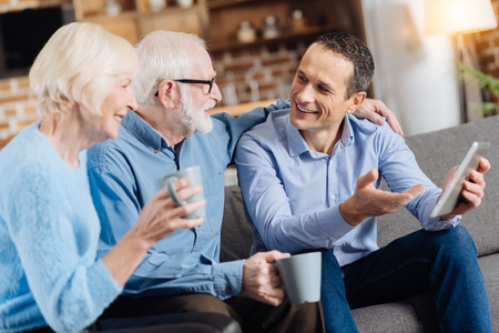 Pleasant discussion. Handsome young man sitting on the sofa next to his senior parents, holding a tablet in his hand and having a discussion with them while they drinking coffee Banco de Imagens