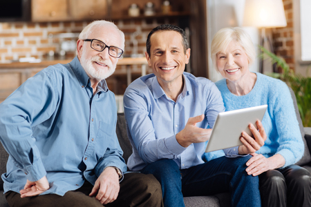 Happy students. Cheerful young man sitting on the sofa between his elderly parents and smiling at the camera together with them while teaching them how to use a tablet