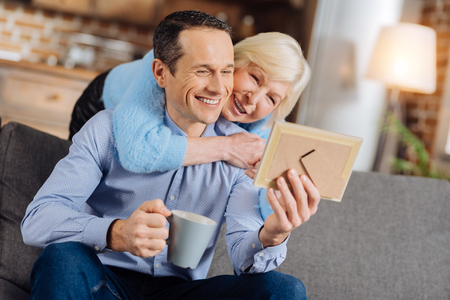 Cozy day. Loving elderly mother hugging her son from behind while he sitting on the couch, drinking coffee and looking at his baby photo in a frame