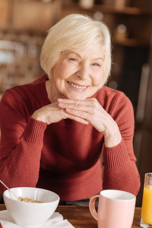 Pure happiness. The portrait of an upbeat senior woman posing for the camera, smiling happily, while sitting at the kitchen table and having breakfast