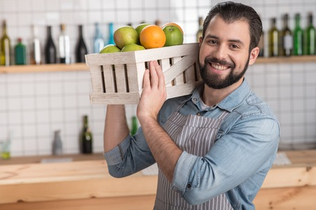Fresh fruit. Handsome responsible enthusiastic worker looking not tired while holding a heavy wooden box with tasty fresh fruit and smiling cheerfully Stock Photo