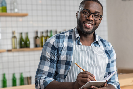 Cheerful mood. Pleasant young handsome waiter having a productive day at work while standing and making notes in a special notebook Stock Photo
