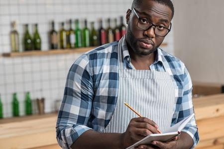 Smart waiter. Responsible reliable smart waiter looking serious while standing in a cafe and making notes in a special notebook Stock Photo