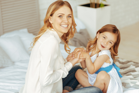 Loving mother. Happy positive attractive woman sitting on the bed and holding her daughters hands while expressing her feeling Reklamní fotografie