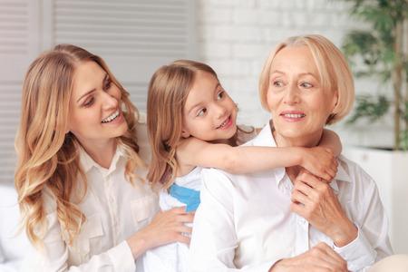 3世代陽気なポジティブなかわいい女の子は、彼女の母と祖母と一緒に座って、彼らと一緒に楽しみながら笑顔