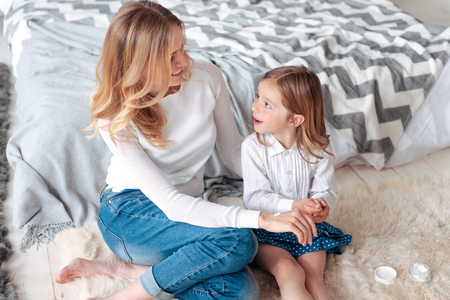 Happy motherhood. Delighted pretty nice girl sitting on the floor and looking at her mom while asking her a question
