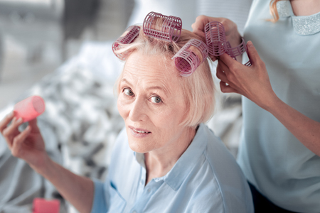 New hairstyle. Pleasant nice elderly woman wearing hair rollers and looking at you while waiting for her new hairstyle to be done