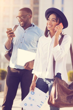 On the phone. Pleasant nice good looking woman holding a bag and walking while having a phone conversation Stock Photo