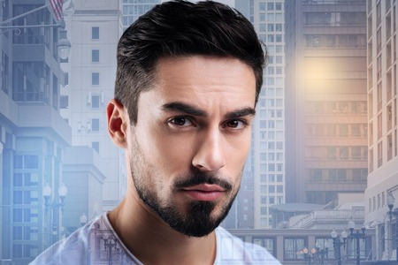 Attractive person. Pleasant calm bearded man looking in front of himself while standing against the urban background and waiting for his beautiful young girlfriend