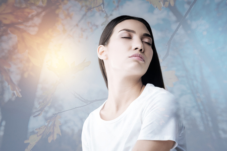 Meditation. Beautiful relaxed young woman sitting with her eyes closed and feeling calm while practicing yoga alone in a lovely garden Stock Photo