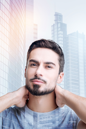 Feeling pleased. Pleasant young bearded man feeling satisfied after using new shampoo of a good quality and standing with his hands on his neck