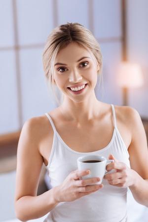 Morgenkaffee genießen . Das Porträt einer hübschen jungen Frau in einem weißen Trägershirt , der über die Kamera aufwirft , während eine Tasse Kaffee mit beiden Händen hält