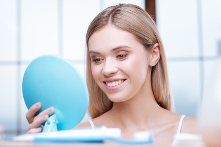 Nice smile. Pleasant young woman holding a blue mirror and checking her teeth while looking into it