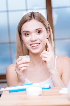 Taking care of skin. Pleasant cheerful young woman applying facial cream to her cheek while smiling brightly