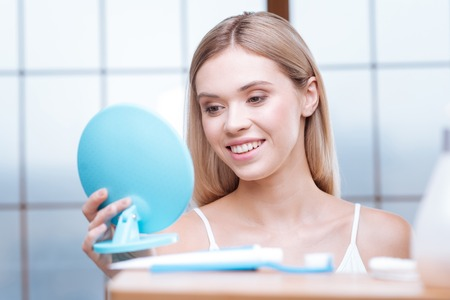 I am pretty. Attractive fair-haired young woman holding a blue mirror and looking into it, smiling at her own reflection Banco de Imagens