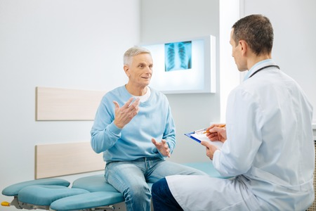 Health problems. Nice pleasant elderly man sitting on the bed and gesticulating while telling the doctor about his problem
