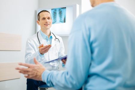 Professionele specialist. Opgetogen aardige professionele specialist zittend op de stoel en wijzend naar zijn patiënt terwijl hij zijn aantekeningen vasthoudt Stockfoto