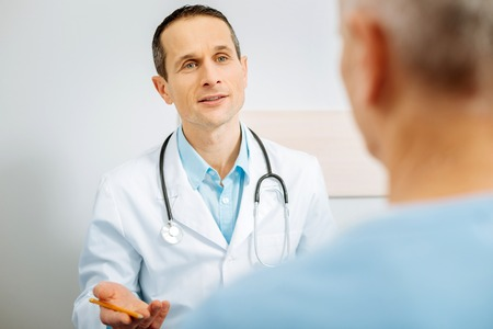 Medical explanation. Nice pleasant male doctor wearing stethoscope and looking at his patient while explaining him the diagnosis