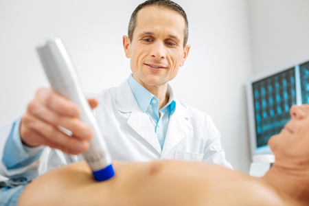 Professional medical checkup. Professional smart male doctor standing near his patient and using medical equipment while checking his health