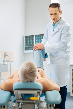 Physiological therapy. Delighted professional male physician standing near his patient and holing his leg while doing physiological therapy