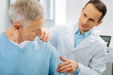 Do you feel anything. Cheerful positive handsome doctor holding patients arm and checking it while standing behind his elderly patient