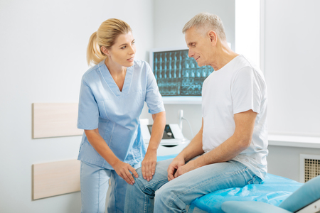 Professional treatment. Positive friendly nice therapist standing near her patient and talking to him while checking his leg Stock Photo