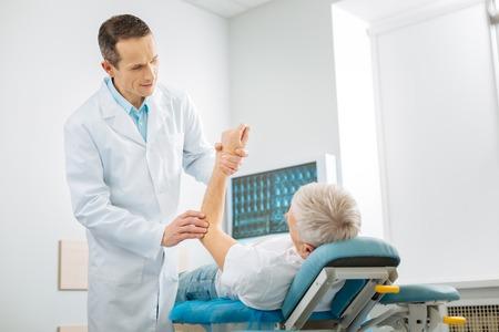 Esame professionale. Terapista abile allegro positivo che sta nel suo ufficio e che controlla la salute dei pazienti mentre facendo il suo lavoro Archivio Fotografico
