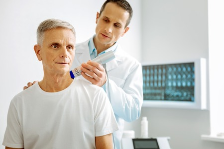 Medical examination. Serious nice elderly patient sitting in the doctors office and being examined while caring about his health