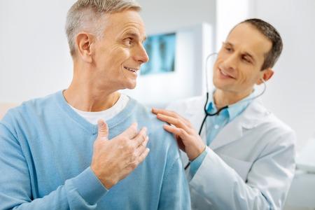 Optimistisch zijn. Vrolijke opgetogen positieve mens die en zich naar zijn arts glimlachen draaien terwijl optimistisch het voelen Stockfoto