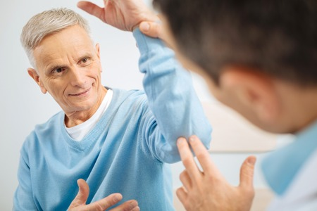 Nothing serious. Positive joyful elderly man sitting opposite his doctor and smiling to his while raising his arm