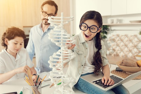 Young scientist. Smart positive cute girl holding laptop and feeling excited while looking at the DNA model