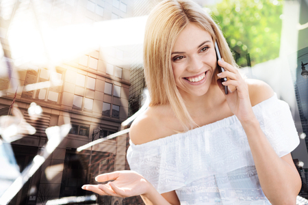 Chit chatt. Wonderful pleasant appealing  woman laughing while looking aside and taking on the phone Фото со стока - 91652962