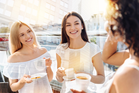 Coffee with friends. Three amazing happy female friends talking while grinning and sipping coffee