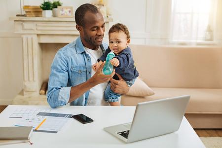 te quiero. Dedicado amar afroamericano padre sosteniendo a su pequeño hijo y alimentarlo mientras está sentado en la mesa con su computadora portátil